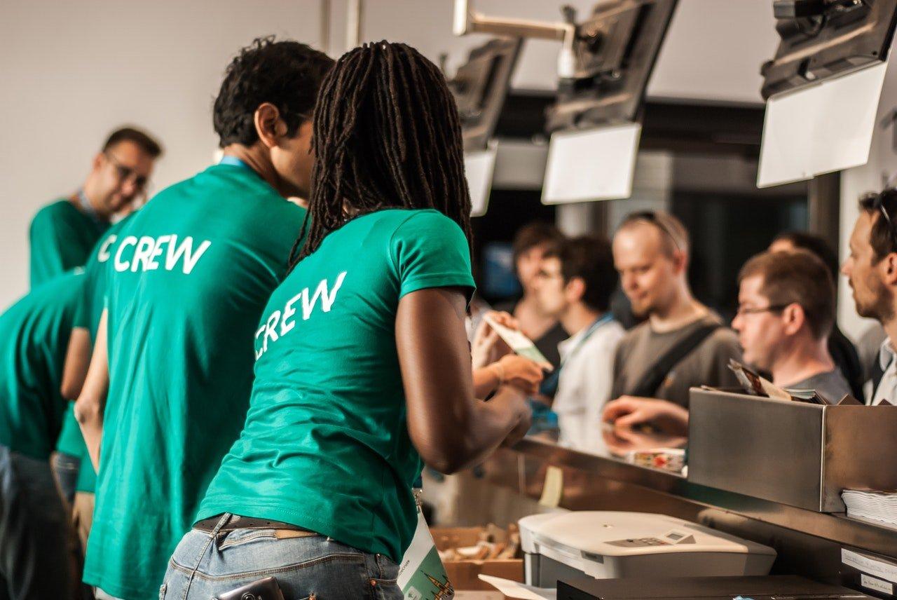 crew members assisting existing customers