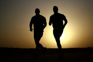 Two people perspirating while running at sunset