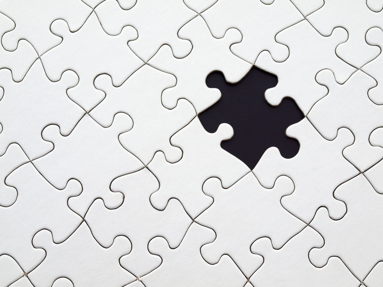 white puzzle with one piece missing that stands out