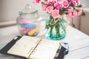 planner open on a table with a vase of flowers
