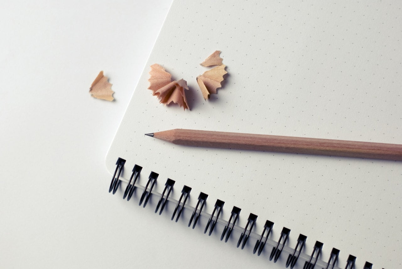 Just sharpened pencil on a plain white paper notebook