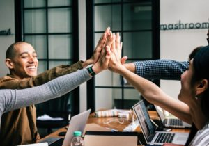 Work group of men and women high five over the discussion of B2B sales