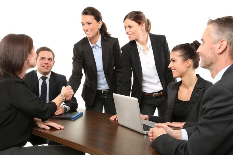 Group of friendly business men and women shaking hands with no friction