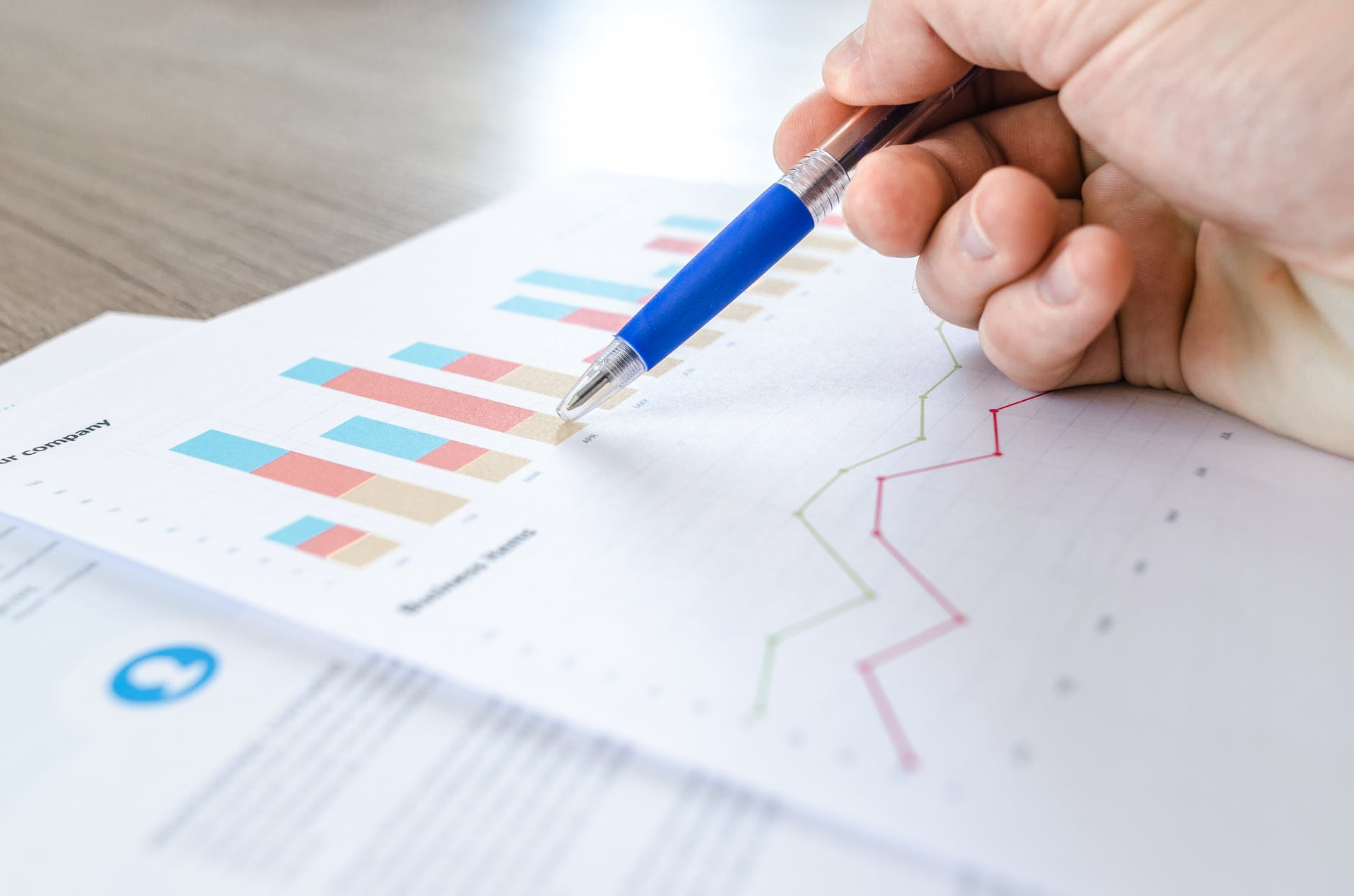 hand with pen pointing to graph that shows sales growth